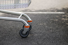 Shopping cart wheels. The front wheels of a shopping cart in a store parking lot royalty free stock photo