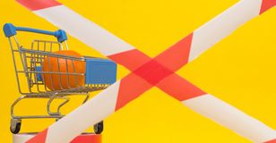 Shopping cart in which lies the mandarin, banned tape, the concept of sanctions on the import of goods and products. Background royalty free stock images