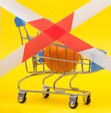 Shopping cart in which the mandarin is fenced with a banned tape, sanctions on products, prohibition, close-up. Shopping cart in which the mandarin is fenced royalty free stock image