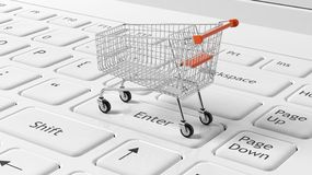 Shopping cart on white laptops Royalty Free Stock Images