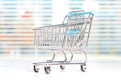 Shopping cart on a white table. Royalty Free Stock Images