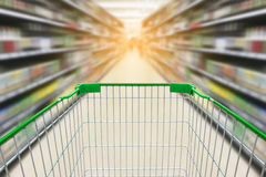 Shopping cart with wine bottles on liquor shelves in supermarket Royalty Free Stock Photo