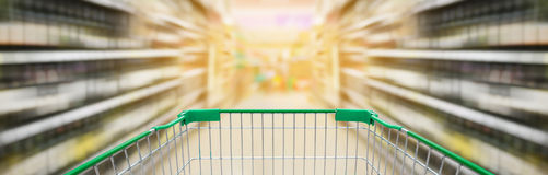 Shopping cart with wine bottles shelves in supermarket aisle. Shopping cart view with wine bottles on liquor shelves in supermarket aisle motion blur panorama Royalty Free Stock Photos