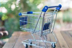 Shopping cart on wood table. For shopping online concept Stock Photography