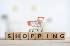 Shopping cart on a wooden sign Stock Image