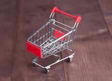 Shopping cart on wooden surface. Stock Photo