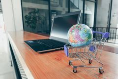 Shopping cart with world globe balloon map for retail business on notebook. Image use for online and offline shopping. Marketing place world wide concept royalty free stock image