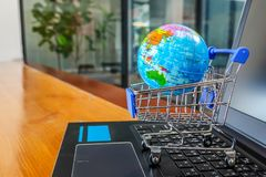 Shopping cart with world globe balloon map for retail business on notebook. Image use for online and offline shopping. Marketing place world wide concept royalty free stock photos