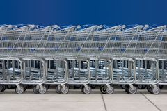 Shopping Carts #1. A line of shopping carts against a blue wall royalty free stock photos