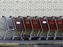 Shopping Carts. A group of shopping carts by the wall of a grocery store Stock Photos