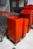 Shopping carts and baskets. Rows of aligned shopping carts and red baskets stock images