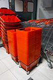 Shopping carts and baskets. Rows of aligned shopping carts and red baskets stock image