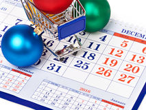 Shopping carts and Christmas balls on calendar Stock Images