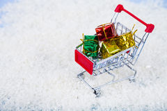 Shopping carts with Christmas gifts in the snow. Concept of Chri Royalty Free Stock Photo