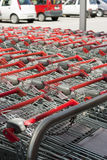 Shopping carts at mall. Empty shopping carts in a row ,blurred cars as background Stock Image