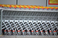 Shopping carts. A row of parked shopping carts equipped with coin-operated locking mechanisms Stock Photography