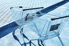 Shopping carts in a store parking lot. Blue toning Royalty Free Stock Photos
