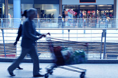 Shopping center. People walking with a shopping cart in a commercial center - motion blur stock images