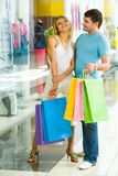 In the shopping center. Portrait of two happy people holding bags and standing in the shopping center royalty free stock images