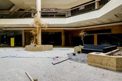 Shopping Center - Abandoned Randall Park Mall - Cleveland, Ohio. A view of the a dead tree in the center concourse inside the abandoned Randall Park Mall near Royalty Free Stock Image