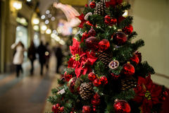 Shopping center with Christmas tree. Decorated with cones, flowers and red balls Stock Image
