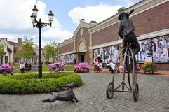 Shopping center styled Dutch village, sculpture of man on bicycle and dog Royalty Free Stock Image