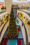 Shopping center-tall Christmas tree- Nuremberg, Germany. Shopping center decorated with golden baubles, escalators, customers, sales Stock Photos