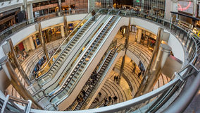 A shopping centre in Canary Warf, London. Fish eye view of escalators with people rushing through in a shopping centre in Canary Warf, London Stock Image