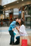 Shopping Centre. Child Giving Presents To Mother. Shopping Centre. Child Buying And Giving Presents To Beautiful Mother In Mall. High Resolution stock image