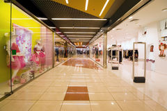 Shopping centre corridor. Shops with wide choice of clothes stock images