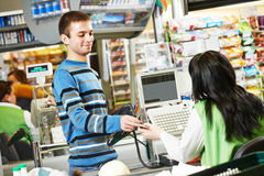 Shopping. Check out in supermarket store. Customer buying food at supermarket and making check out with cashdesk worker in store Stock Photos