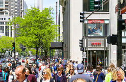 Shopping in Chicago. Chicago, USA - May 24, 2014: A crowded shopping street with lots of pedestrians, some green trees an Retail-Shops Stock Images