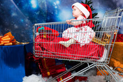 Shopping for christmas. Christmas child sitting in a supermarket trolley against night stellar sky Stock Images
