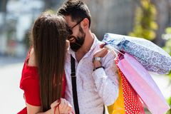 LOVELY COUPLE SHOPPING IN THE CITY AND KISSING. Shopping in the city. Lovely couple having fun on the Macedonian streets, on a sunshine day royalty free stock images