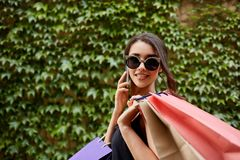 Shopping. Close up portrait of young attractive tan-skinned caucasian girl in sunglasses and black dress holding lot of Royalty Free Stock Image