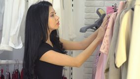 Shopping in a clothing store - a young woman updates her wardrobe.  stock video footage