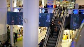 Shopping com povos que andam e se movem na escada rolante vídeos de arquivo