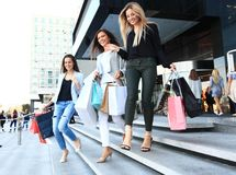 Beautiful girls with shopping bags walking at the mall. Royalty Free Stock Photos