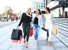 Beautiful girls with shopping bags walking at the mall. Stock Photo