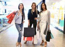 Beautiful girls with shopping bags walking at the mall. Royalty Free Stock Image
