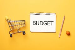 Shopping concept. Budget concept. shopping cart,  blank paper notebook with pen on a yellow background stock photos