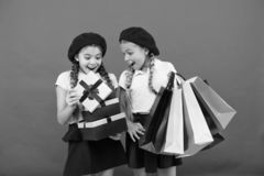 Shopping concept. Child cute small girls on shopping tour. Best price. Buy now. Visit shopping mall. Kids girls hold. Bunch shopping bags or birthday gifts stock photography
