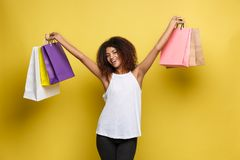 Shopping Concept - Close up Portrait young beautiful attractive African woman smiling and joyful with colorful shopping. Bag. Yellow Pastel wall Background Stock Photos