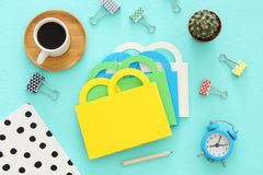 Shopping concept with paper bag and office supply. Flat lay, Top view. Stock Photos