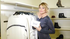Shopping concept. Portrait of Stylish and fashionable girl holding silver sale sign in fashion boutique and smiling at
