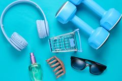 Shopping concept. Headphones, dumbbells, toy shopping trolley, bottle of perfume, sunglasses on a blue background. Top view royalty free stock images