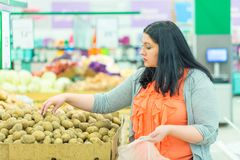 Shopping concept. Woman choosing and taking potatoes in the supermarket store. royalty free stock photography