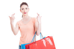 Shopping concept with woman showing fingers crossed holding pape Royalty Free Stock Photos