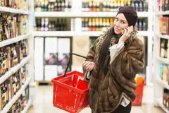 Shopping concept. Woman speaking phone and holding red shopping basket in the supermarket store near wine bottles windows. royalty free stock images