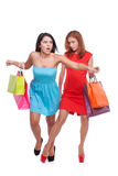 Shopping confrontation. Young red hair women makes her friend tripping up while holding shopping bags Stock Photography
